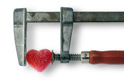 Heart in clamp. Heart healing concept - red heart in the vice tool Stock Photo