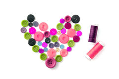 Heart of clothes buttons with sewing thread Royalty Free Stock Image