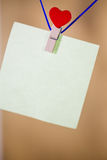 Heart clothes peg holding note. With blank copy space royalty free stock image