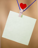 Heart clothes peg holding note. With blank copy space stock photo