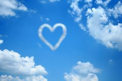 Heart in the Clouds. A heart made of clouds sits in the middle of a blue sky and white clouds Royalty Free Stock Photo