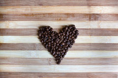 Heart of coffe beans on wooden background Stock Image