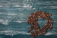 Heart of coffee beans on a blue wooden old background. Space for text. Valentine`s Day stock image