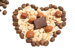 Heart of coffee beans, chocolate, peanuts and hazelnuts. On white royalty free stock photography