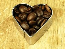 Heart and Coffee beans close up on wooden oak table Stock Photo