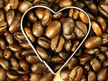 Heart and Coffee beans close-up on wooden, oak table. Stock Images