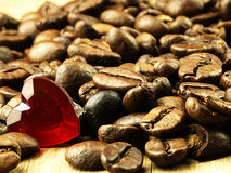 Heart and Coffee beans close-up on wooden, oak table. Royalty Free Stock Image
