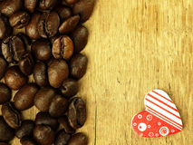 Heart and Coffee beans close-up on wooden, oak table. Royalty Free Stock Images