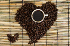Heart from coffee beans with coffee cup on japan mat Royalty Free Stock Photo
