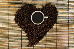Heart from coffee beans with coffee cup on japan mat.  Royalty Free Stock Photography