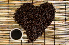 Heart from coffee beans with coffee cup on japan mat.  Royalty Free Stock Photo