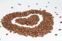 Heart of coffee beans. Coffee grains are scattered royalty free stock photos
