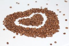 Heart of coffee beans. Coffee grains are scattered royalty free stock photo