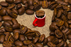 Heart of coffee beans and a Cup on burlap background Royalty Free Stock Photo