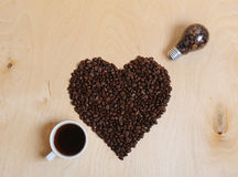Heart of coffee beans, a cup of coffee and a light bulb with coffee beans inside in the form of a piercing arrow. Heart of coffee beans. Cup of coffee and a Stock Images