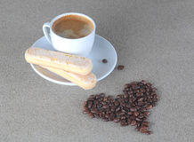 Heart of coffee beans with cup espresso and savoiardi biscuits. Heart of beans with coffee cup Royalty Free Stock Image