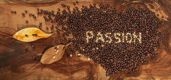 A heart of coffee beans with dry leaves of magnolia Stock Images