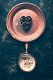 Heart of coffee beans and hot coffee drink in a vintage cup on a rustic dark background. Valentine`s Day.Top view.  stock photos