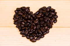 Heart coffee beans lay on the brown background. Little heart coffee beans over the brown background royalty free stock image