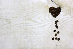 Heart of coffee beans on light wooden background. royalty free stock photography