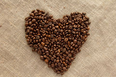 Heart of coffee beans on linen top view Stock Images
