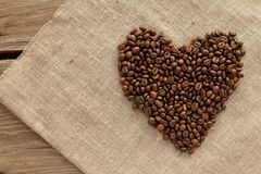 Heart of coffee beans on linen top view Royalty Free Stock Photography