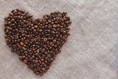 Heart of coffee beans on linen top view Stock Image