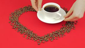 Heart of coffee beans on a red background. Female hands putting cup of coffee. Heart of coffee beans on a red background. Female hands putting cup of coffee stock video footage