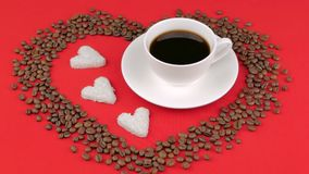 Heart of coffee beans on a red background. Female hands putting cup of coffee. Heart of coffee beans on a red background. Female hands putting cup of coffee stock footage