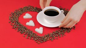 Heart of coffee beans on a red background. Female hands putting cup of coffee. Heart of coffee beans on a red background. Female hands putting cup of coffee stock video