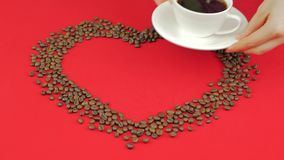 Heart of coffee beans on a red background. Female hands remove cup of coffee. Heart of coffee beans on a red background. Female hands remove cup of coffee stock video