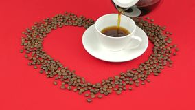 Heart of coffee beans on a red background. Pouring coffee into a cup. Heart of coffee beans on a red background. Pouring coffee into a cup stock video