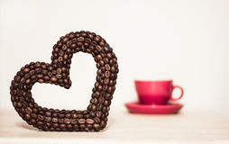 Heart of the coffee beans and red or pink cup Royalty Free Stock Images