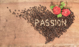 A heart of coffee beans with red roses. Stock Photos