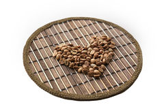 Heart of coffee beans on a round matting Royalty Free Stock Image