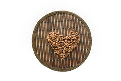 Heart of coffee beans on a round matting Royalty Free Stock Photos