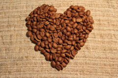 Heart of coffee beans on sacking. Heart of coffee beans on coarse cloth stock photography