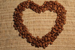 Heart of coffee beans on sacking. Heart of coffee beans on coarse cloth stock image