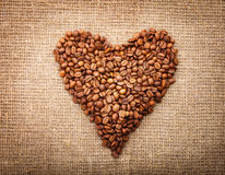 Heart from coffee beans on textured brown sack Stock Image