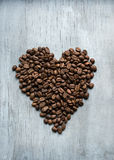 Heart of coffee beans on the wooden background Royalty Free Stock Image