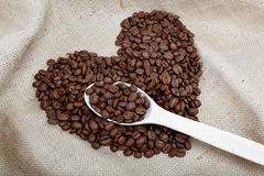Heart of the coffee beans and wooden spoon. Heart of the coffee beans and wooden spoon on sacking Royalty Free Stock Photo