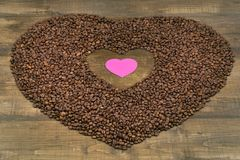 Heart of coffee beans on a wooden surface. Coffee beans in the shape of heart on a wooden background with place for text. Postcard, blank, template for St Royalty Free Stock Image