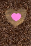 Heart of coffee beans on a wooden surface. Coffee beans in the shape of heart on a wooden background with place for text. Postcard, blank, template for St Stock Image