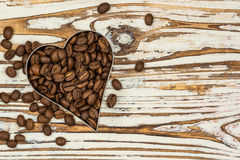 Heart coffee frame made of coffee beans on wooden texture Royalty Free Stock Photo