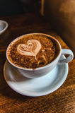 Heart Coffee. Latte art, coffee on the wooden desk as background Royalty Free Stock Photos