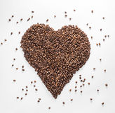 Heart from coffee with scattered beans isolated on a white background Royalty Free Stock Photo