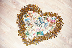 Heart of coins and money on wooden background Stock Image
