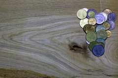 Heart of coins on wooden background. Stock Image