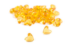 Heart color pills of fish oil Stock Photos