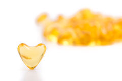 Heart color pills of fish oil Royalty Free Stock Images